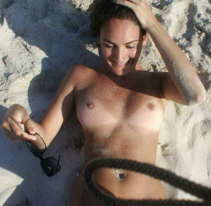 Happy girl with sand on her boobs