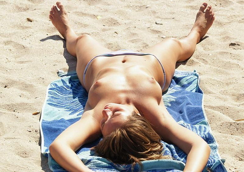 Topless pretty damsel cook herself on the beach