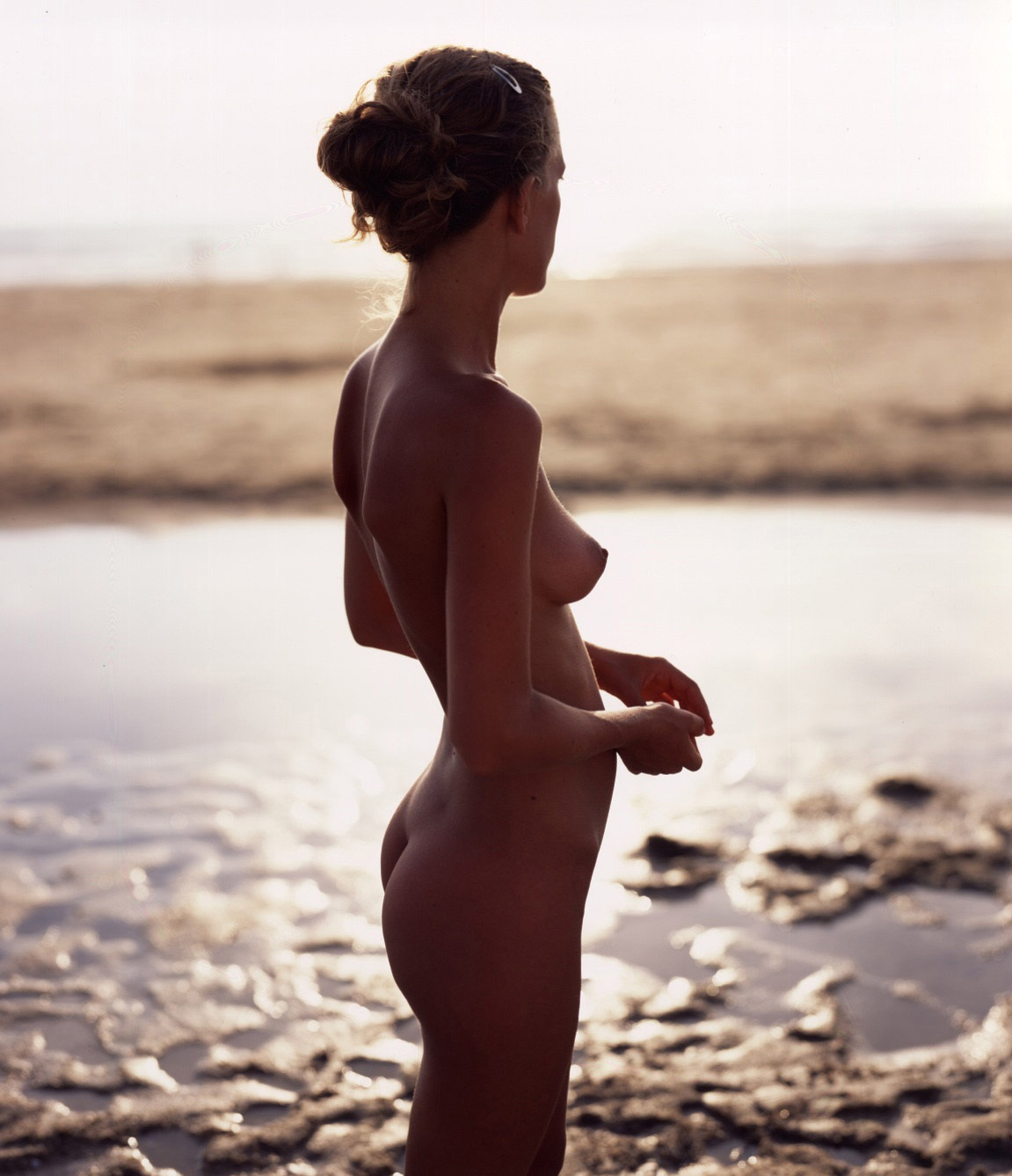 Nude hottie on an empty beach watching sunset