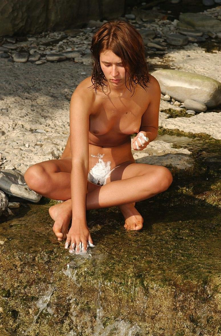 Nude girl shaving her pubes near the sea