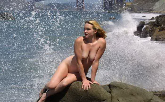 Posing on a rocky beach with splashing water around