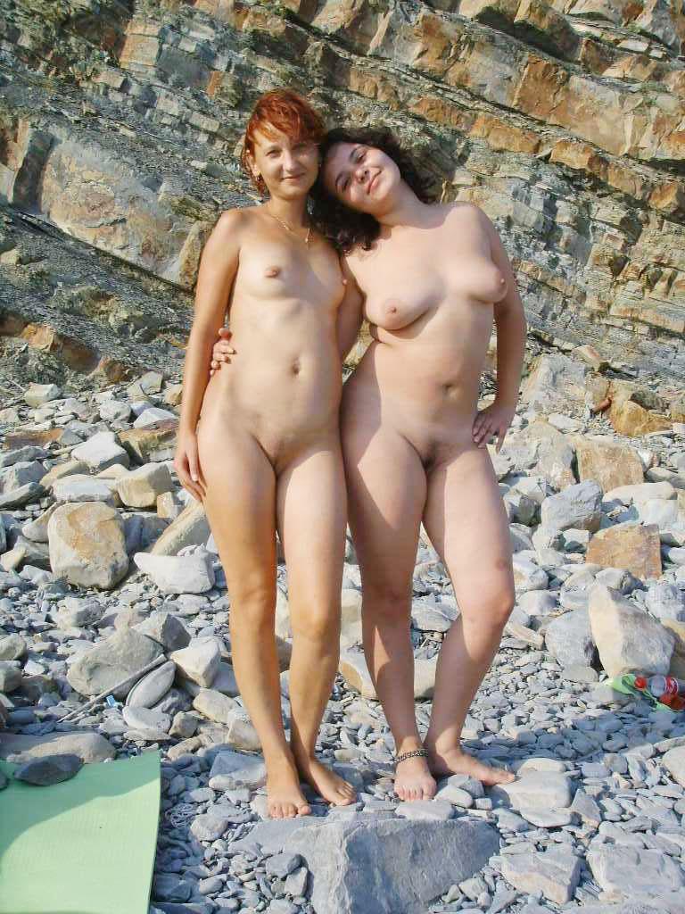 Nude girlies posing on an empty beach