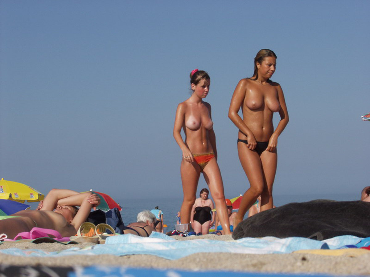 Topless cuties walking on the beach