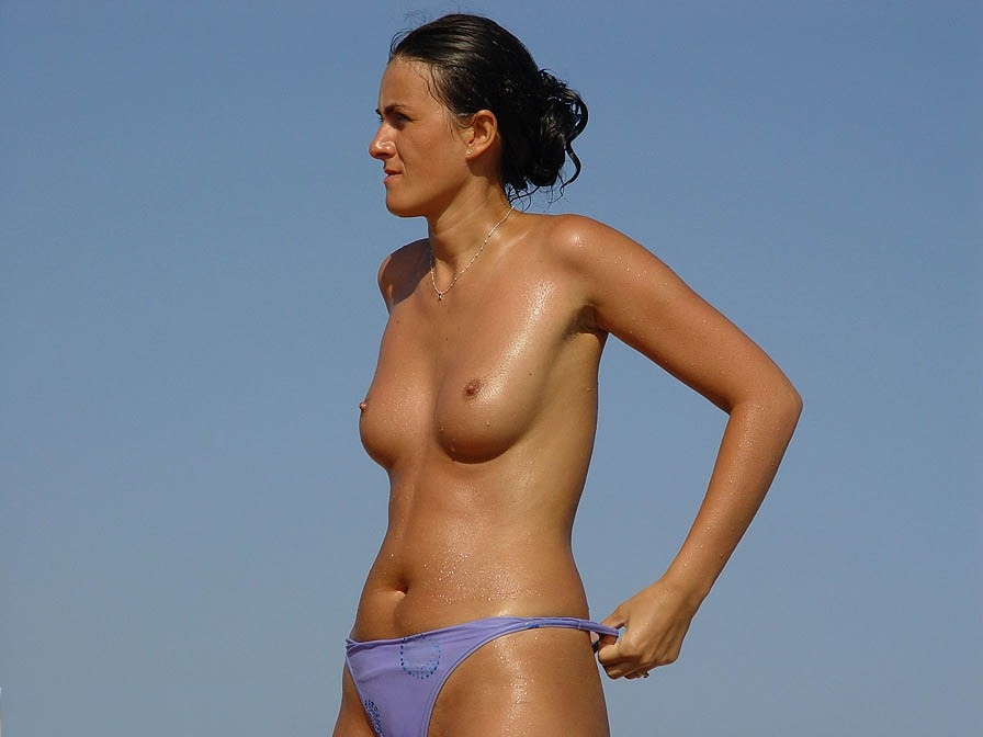On the beach admiring this topless beautiful girl