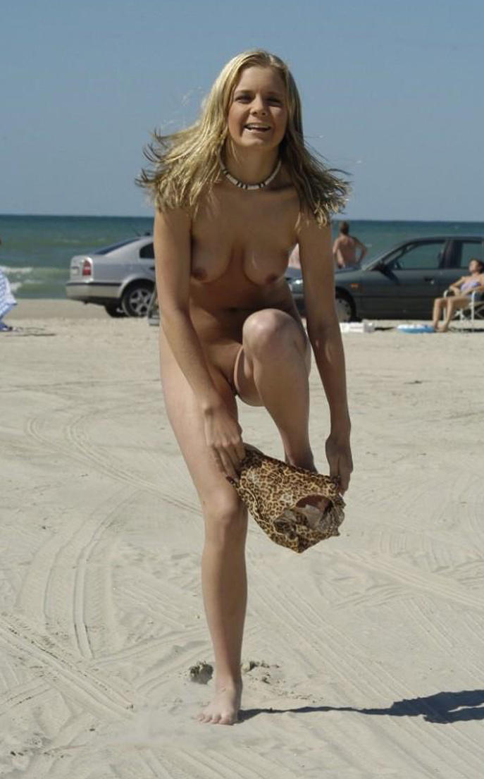 Frisky blonde undressing on the beach