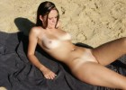 Nude babe getting a good tan on the beach