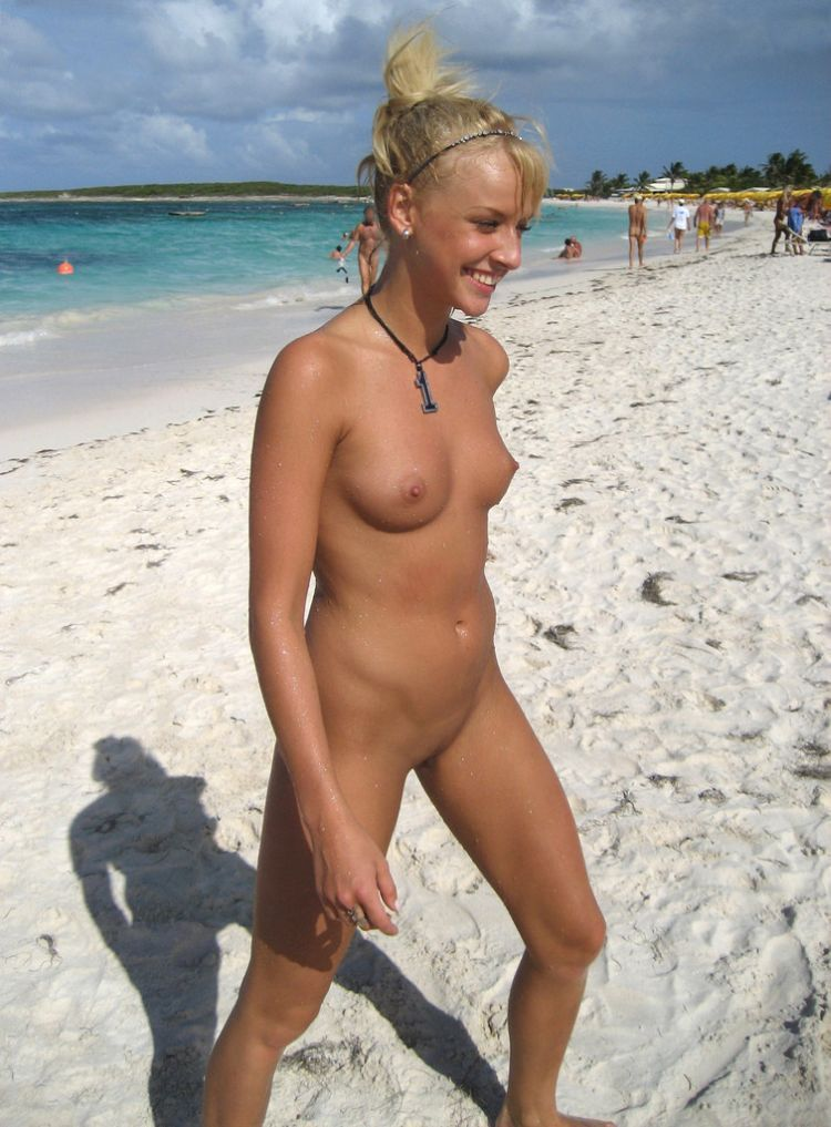 Nude blonde hottie smiling and walking on beach