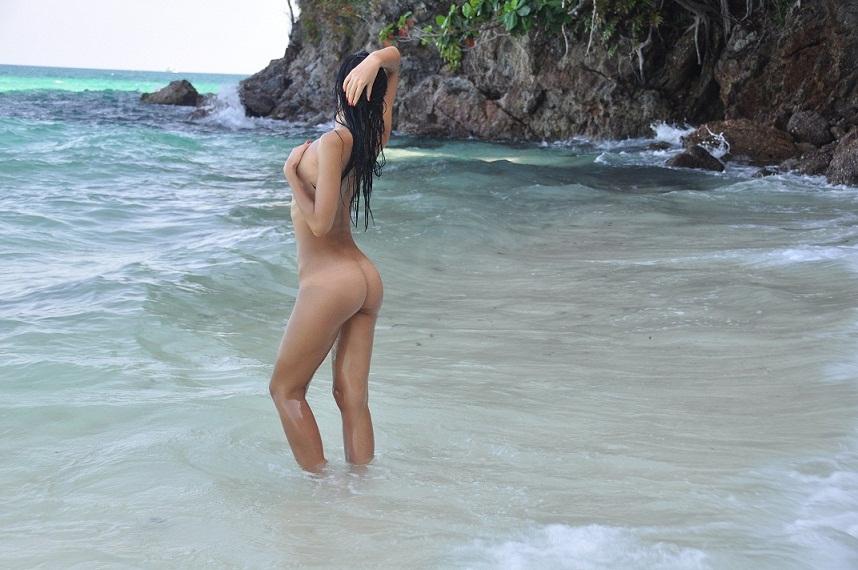 Nudist girl returning on blue lagoon
