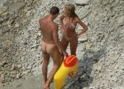 Nudist couple exposed on a rocky beach