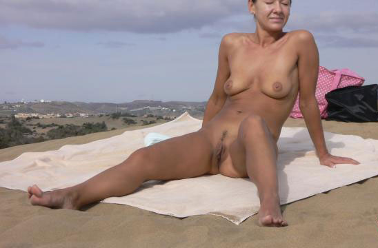 Sexy older woman spreading her legs on the beach