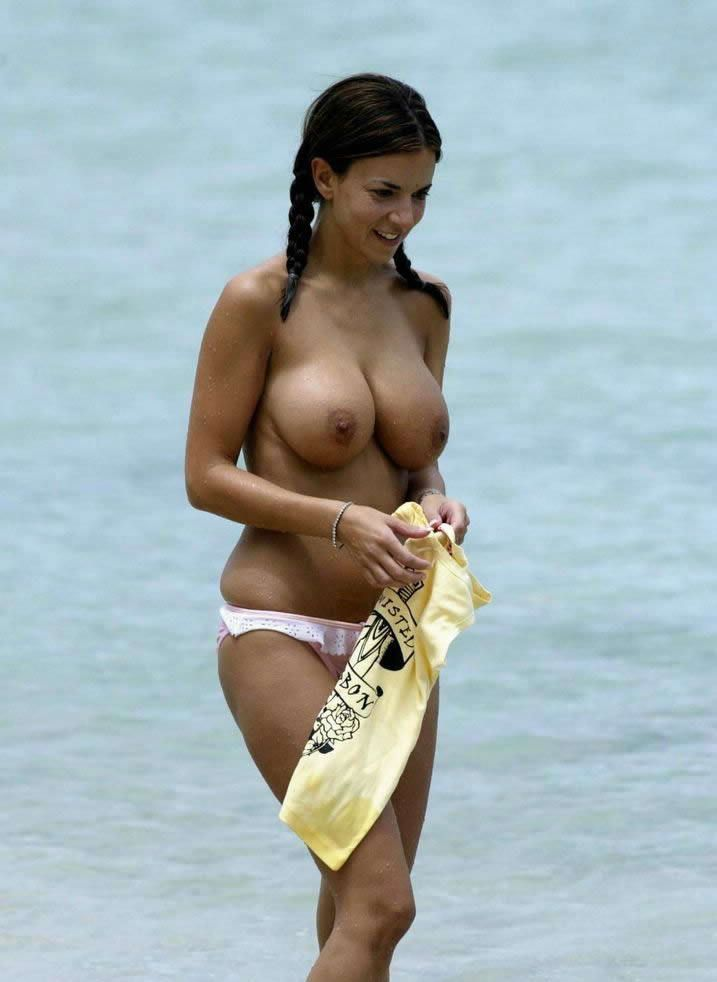 Topless curvy brunette in pigtails at the beach