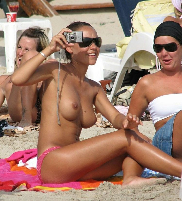 Topless hottie snapping pics at the beach
