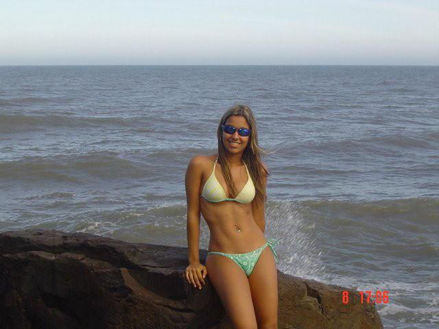 Hot babe in bikini stands on a rock