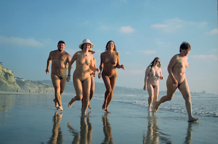 Running nude and wild on an empty beach