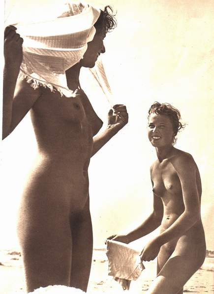 Two nude women playing on the beach