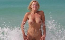 611-Flirty-blonde-splashing-nude-in-the-surf.jpg