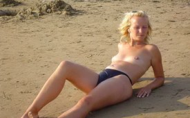 912-Topless-blonde-babe-laying-on-the-sand.jpg