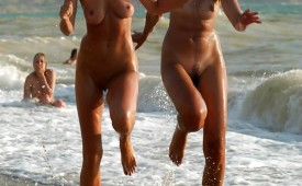 936-Two-hot-naked-friends-taking-a-playful-jog-through-the-surf.jpg