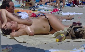 944-Topless-oiled-babe-tanning-her-boobs-at-beach.jpg